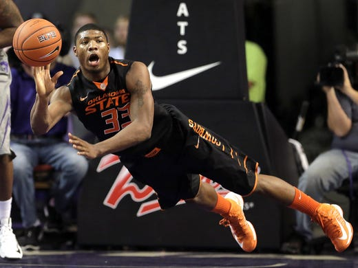 Oklahoma State guard Marcus Smart passes the ball during the first half of his team's game against Kansas State earlier this season in Manhattan, Kan.