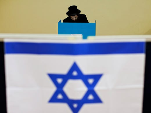 An ultra-Orthodox Jewish man votes on Jan. 22 in Bnei Brak, Israel. People are voting in a parliamentary election that is expected to return Prime Minister Benjamin Netanyahu to office despite years of stalled peace talks with the Palestinians and mounting economic problems.