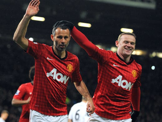 Manchester United midfielder Ryan Giggs celebrates with English forward Wayne Rooney after scoring a penalty during the English FA Cup football match between Manchester United and Fulham at Old Trafford in Manchester on Jan. 26, 2013. Manchester United won 4-1.