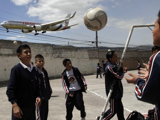 Students play soccer at the Eloy Alfaro school as a plane approaches the Mariscal Sucre airport in Quito, Ecuador. On Feb. 19, the airport will close and a new airport will be built in an agricultural setting 12 miles northeast of the city.