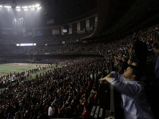 A fan looks around the Superdome after the lights went out during the second half of Super Bowl XLVII.