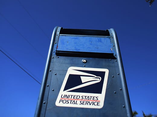 A U.S. Postal Service mailbox stands out against a blue sky on Nov. 15 in Miami. The U.S. Postal Service will stop delivering mail on Saturdays, starting in August, in a plan to save the financially struggling agency $2 billion.