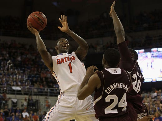 Florida guard Kenny Boynton (1) drives to the hoop against a pair of Mississippi State defenders in Gainesville, Fla. Boynton scored 10 points to help the No. 2 Gators roll to an 83-58 win.