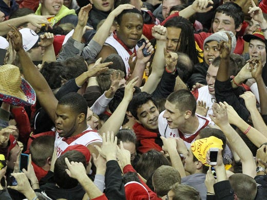 Maryland Terrapins fans celebrate with forward Charles Mitchell, top, center Shaquille Cleare, left, and center Alex Len after their 83-81 win over the Duke Blue Devils at the Comcast Center.