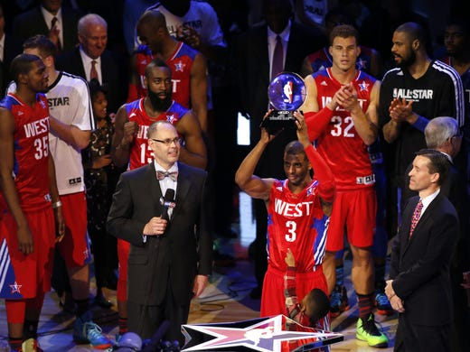 Chris Paul hoists the All-Star Game MVP trophy. The Clippers point guard led the Western Conference to a 143-138 win Sunday against the Eastern Conference in Houston.