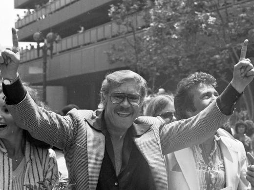 Lakers owner Jerry Buss gestures as the NBA championship team is honored with a parade in Los Angeles in May of 1980. Buss, the Lakers' playboy owner who shepherded the NBA franchise to 10 championships, died Monday at the age of 80.