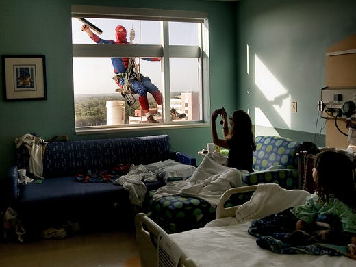 Sao Doan, 5, right, watches as her mom, Tiffany Ringer of Kenneth City, snaps a photo of Merrill Hunt dressed as  Spiderman  as he washes her window at All Children's Hospital in St. Petersburg, Fla.