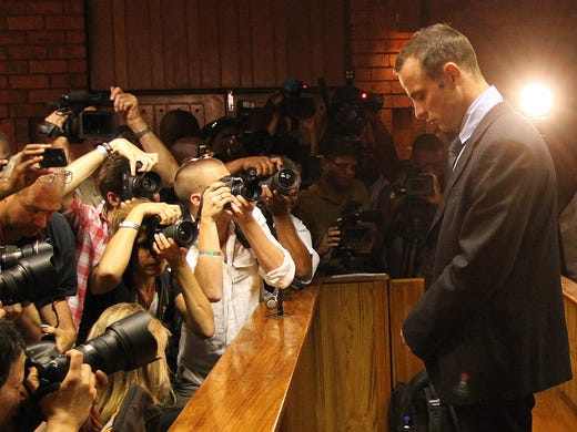 Photographers swarm around Oscar Pistorius as he stands in the courtroom during the fourth day of his bail hearing after he was charged with premeditated murder in the killing of his girlfriend, Reeva Steenkamp.
