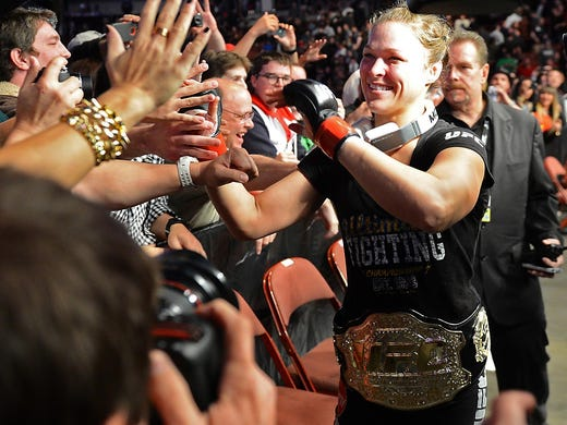 Ronda Rousey celebrates with fans after her fight with Liz Carmouche in their UFC women's world bantamweight championship bout at the Honda Center.