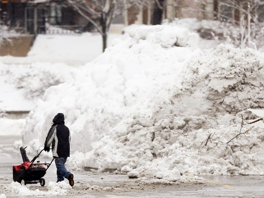 A man tries to clear a giant pile of snow left by road crews in the Country Club Plaza shopping district of Kansas City, Mo.