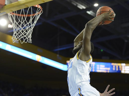 UCLA Bruins guard Kyle Anderson dunks the ball as Arizona Wildcats center Kaleb Tarczewski watches during the second half at the Pauley Pavilion.