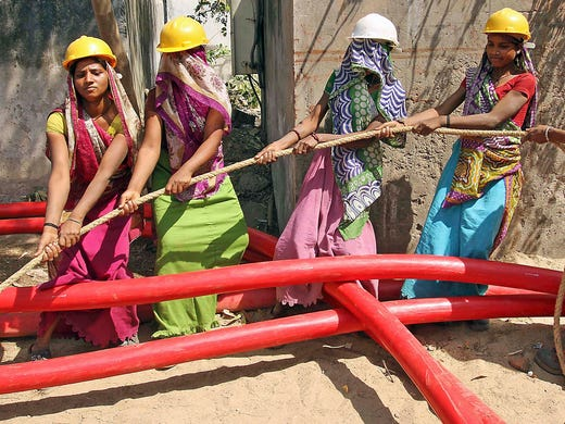 Women workers position an electric cable on International Women's Day on March 8 in Ahmadabad, India.