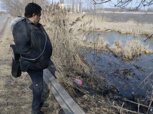 Carol Trimble, a relative of one of the victims, views the pond along Pine Avenue in Warren, Ohio, where six teens were killed in a crash on Sunday.