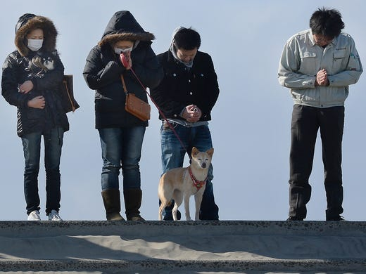 People pray for victims of the 2011 earthquake and tsunami on March 11 in Arahama district in Sendai, Japan. Japanese are marking the second anniversary of the disaster that claimed 19,000 lives and triggered a nuclear accident.