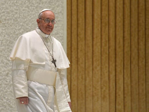 """Pope Francis arrives March 16 at the Paul VI Hall at the Vatican to meet with members of the media for the first time since his election to the papacy. Francis called for """"a poor church for the poor"""" and explained he chose his papal name because St. Francis of Assisi was """"a man of poverty and a man of peace."""""""