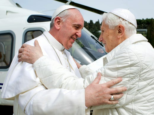 Pope Francis, left, meets Pope Emeritus Benedict XVI on March 23 at the helipad of the papal summer residence in Rome. Pope Francis visited Castel Gandolfo to have lunch with his predecessor.