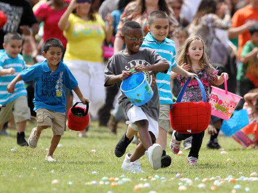 Children rush to collect Easter eggs after the colored eggs were dropped by a helicopter at The Way Church annual Easter egg hunt in Spring, Texas.