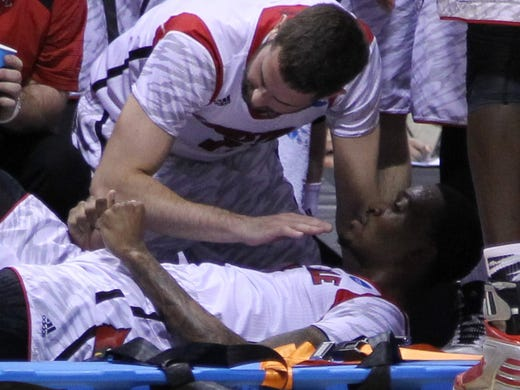 Louisville Cardinals guard/forward Luke Hancock gives encouragement to guard Kevin Ware as Ware is taken off the court on a stretcher in the first half against the Duke Blue Devils at Lucas Oil Stadium.