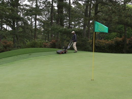 """The 18 greens, among all the other wonders at Augusta National, are perhaps the most memorable partof the tournament for the players. Care of the greens is a painstaking process. Here, Ralph Godbee operates the """"wacky head mower"""" that was invented at Augusta Nationa. The mower cuts grass at the fringe of the green to two different heights."""