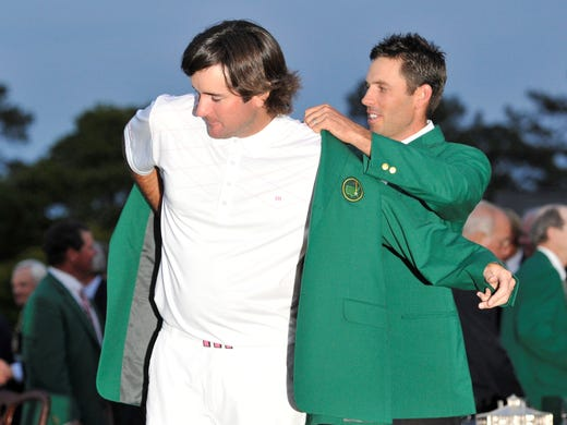 Charl Schwartzel, the 2011 champion, helps 2012 Masters champion Bubba Watson into his green jacket.