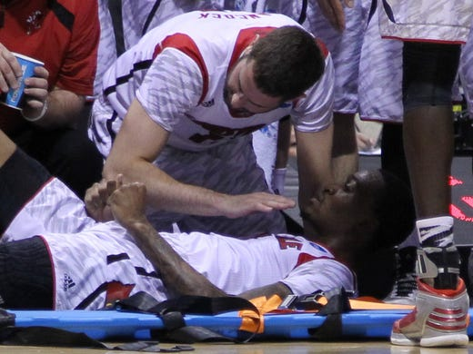 Louisville's Luke Hancock (top) gives encouragement to injured guard Kevin Ware after Ware's gruesome injury during the Midwest regional against Duke. It's been an emotional few days for Ware and his teammates.