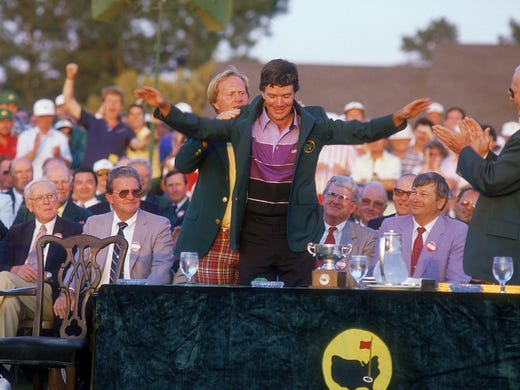 Jack Nicklaus helps Larry Mize into his green jacket.