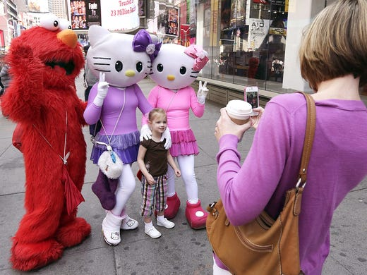A person dressed as Elmo, left, and two Hello Kitty characters pose for photos with a little girl on April 9 at Times Square in New York City. A string of arrests over the past few months has brought unwelcome attention to the growing number of people who make a living by dressing as cartoon characters and charging tourists a few dollars to pose with them.