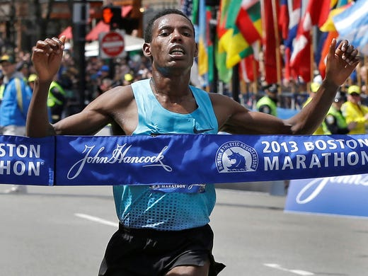 Lelisa Desisa of Ethiopia crosses the finish line to win the men's division of the 2013 Boston Marathon Monday. He finished in 2:10:22, 5 seconds ahead of Micah Kogo of Kenya.