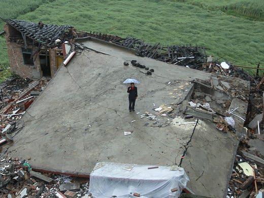 A woman stands on a home that collapsed during a magnitude 7.0 earthquake on April 22 in Longmen township, China.