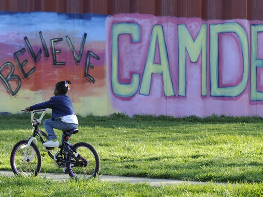 Tyasia Langston, 5, rides her bike past a water tower decorated with the name of Camden N.J. Camden, which statistics show is the poorest and most dangerous city in America, broke a record last year with 67 homicides.