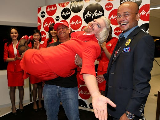 Virgin Group founder Sir Richard Branson poses with with AirAsia Group CEO Tony Fernandes at Perth International Airport on May 12, 2013. Branson lost a friendly bet with Fernandez over which of their Formula One racing teams would finish ahead of the other in the 2010 Formula One Grand Prix. The loser had to serve as a female flight attendant aboard the winner's airline.