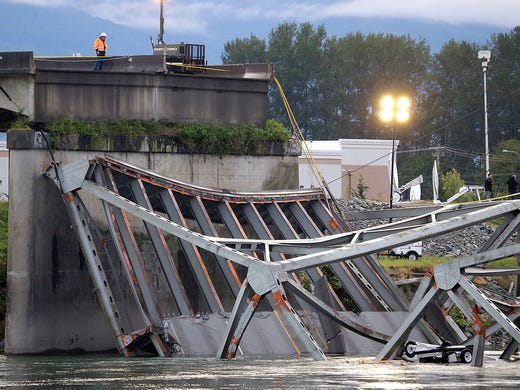 A worker looks at the collapsed section of the Interstate 5 bridge on the Skagit River on May 24 in Mount Vernon, Wash. A truck carrying an oversized load struck the four-lane bridge between Seattle and Canada on May 23, sending a section of the span and two vehicles into the river.
