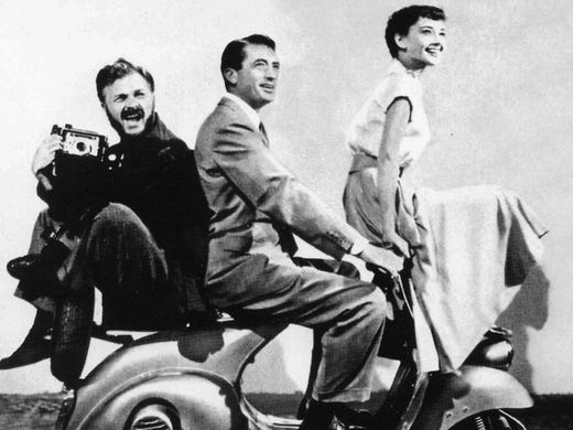 "Actors Gregory Peck and Audrey Hepburn -- with Eddie Albert perched on back -- all sit on a Vespa scooter during the shooting of ""Roman Holiday"" in Rome in 1953."
