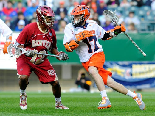 Syracuse Orange attackman Dylan Donahue drives to the goal around Denver Pioneers midfielder Terry Ellis during the first quarter at Lincoln Financial Field.