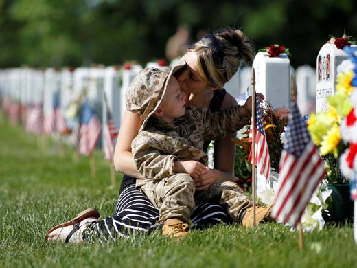 Brittany Jacobs kisses son Chris near the grave site of her husband, Christopher Jacobs, at Section 60 on Memorial Day at Arlington National Cemetery in Arlington, Va., on May 27. Veterans of the Iraq and Afghanistan wars are buried in Section 60.