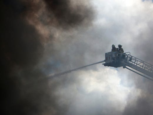Firefighters battle a fire at the Southwest Inn, Friday, in Houston.  A fire that engulfed a Houston motel has injured at least six firefighters, including two critically, and three people are missing.