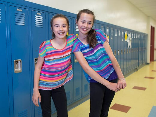 Katie Thomas, left, and her twin sister, Megan, pose for a photograph June 6 at Highcrest Middle School in Wilmette, Ill. The are one of a set of 24 twins at the school and this group is attempting to break a Guinness World record for the number of twins in one grade, which is currently 16 sets.