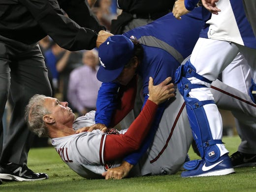Manager Don Mattingly (R) of the Los Angeles Dodgers pushes down coach Alan Trammell of the Arizona Diamondbacks during a bench-clearing brawl in the seventh inning at Dodger Stadium.