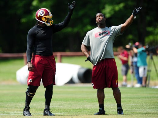 Washington Redskins quarterback Robert Griffin III (left) talks to wide receiver Pierre Garcon (right) during mini camp at Redskins Park.