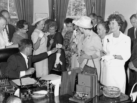 President Kennedy signs the Equal Pay Act on June 10, 1963. The act eliminated pay discrimination based on sex.