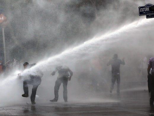 Turkish riot police spray water at demonstrators near Kizilay Square in Ankara, Turkey, on June 16.