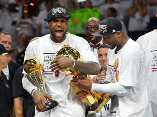 LeBron James holds the Bill Russell NBA Finals MVP trophy in his right arm as he grabs the Larry O'Brien championship trophy with his left. James took his second of each June 20 as the Heat beat the Spurs in seven games.
