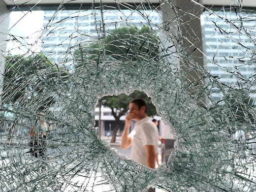 People walk past the shattered window of a bank which was broken during a demonstration on June 21 in Rio de Janeiro. Thousands of Brazilians staged protests in several cities, demanding better public services and condemning massive government spending to stage the World Cup soccer event.
