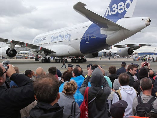 Visitors view an Airbus A380 passenger jet on June 22, 2013, at the Paris Air Show at Le Bourget Airport in France.