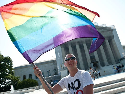 A gay rights activist waves a rainbow flag in front of the Supreme Court on June 15 in Washington, D.C. The iconic flag was designed by Gilbert Baker in 1978.