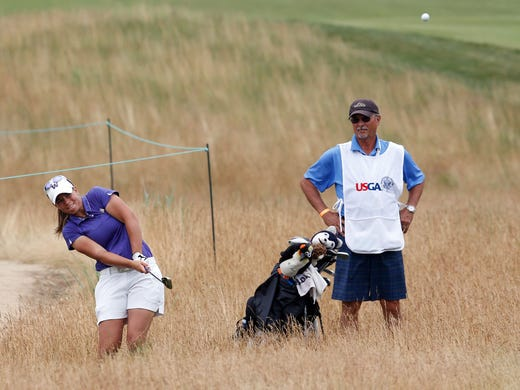 Kelli Bowers hits from the rough as  her caddie Larry Bowers looks on.