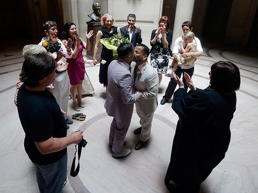 Peter Madril, center right, kisses Monte Young after they were married at City Hall on June 29 in San Francisco. Gay couples waited in line as clerks resumed issuing same-sex marriage licenses, one day after a federal appeals court removed the ban following a Supreme Court ruling.