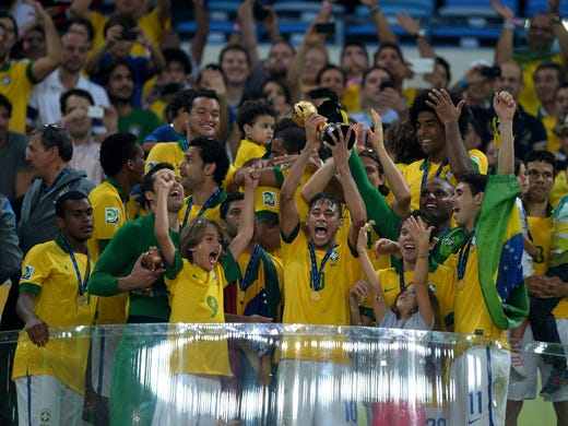 Brazil 3, Spain 0: Championship game -- Neymar of Brazil lifts the trophy with his teammates following their victory.