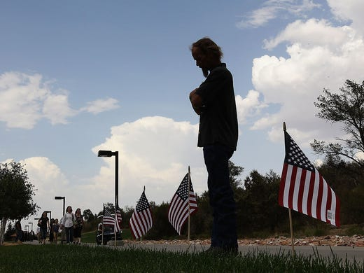 Brian Guffey looks at 19 American flags placed outside an auditoriumat Embry-Riddle University on July 1 in Prescott, Ariz., before the start of a memorial service for 19 firefighters killed while battling a wildfire. The members of the Granite Mountain Hotshot Crew died on June 30 when a fast-moving wildfire overran their position near Yarnell, Ariz.