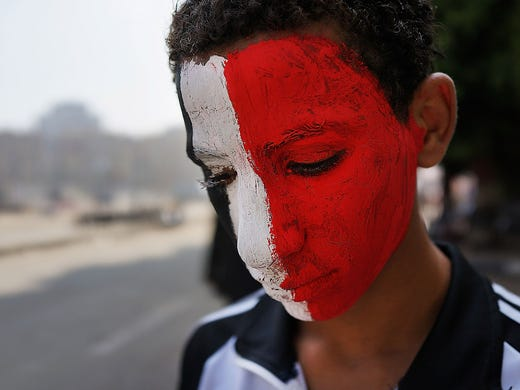 A boy with his face painted with the colors of Egypt's national flag pauses at Tahrir Square on July 4 in Cairo. Adly Mansour has been sworn in as the interim head of state after the military ousted President Mohammed Morsi on July 3.